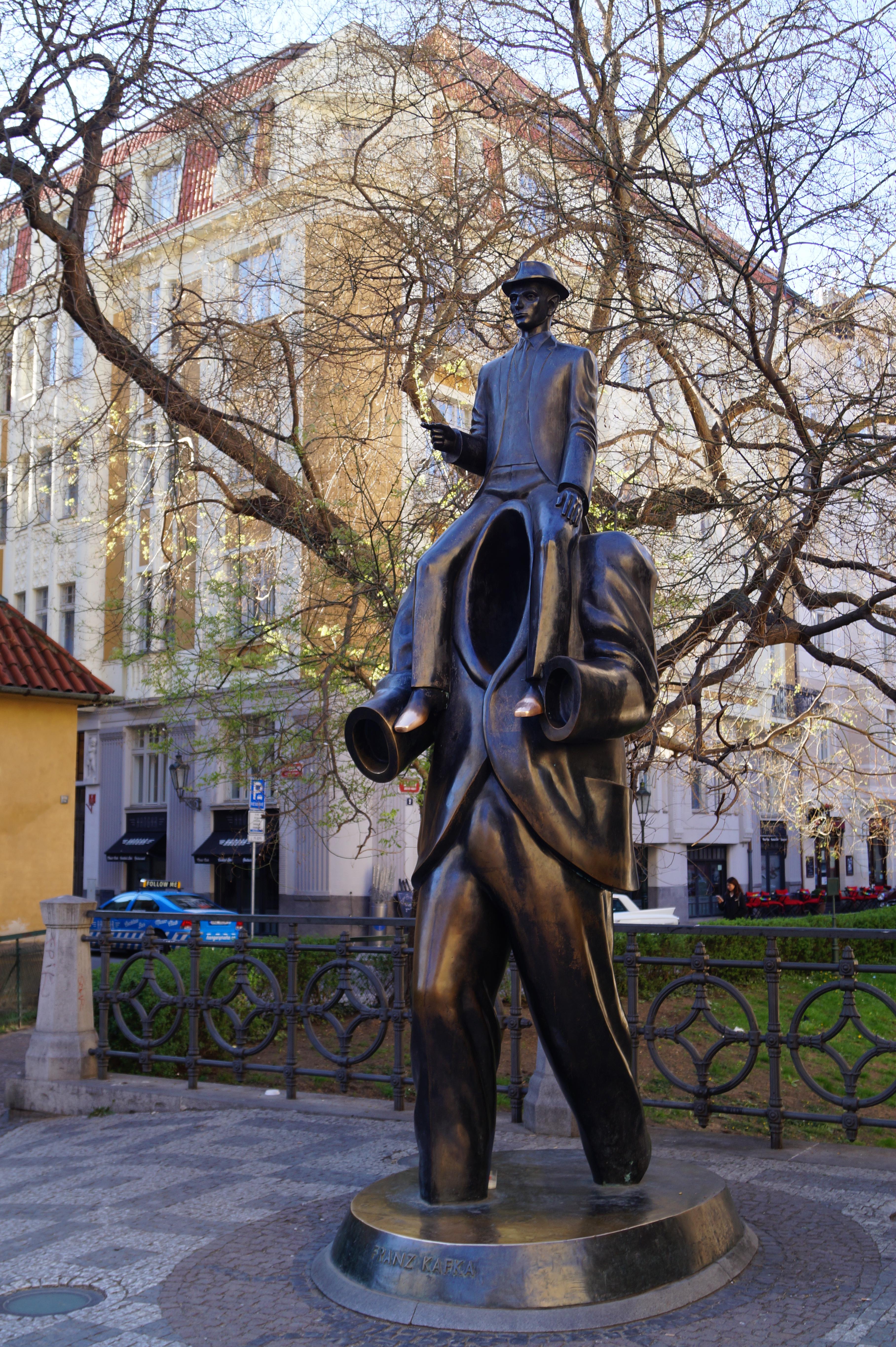 Escultura de Franz Kafka, subido a un gigante invisible.